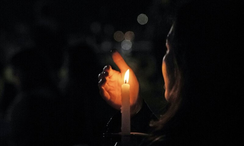 Image of a woman holding a candle