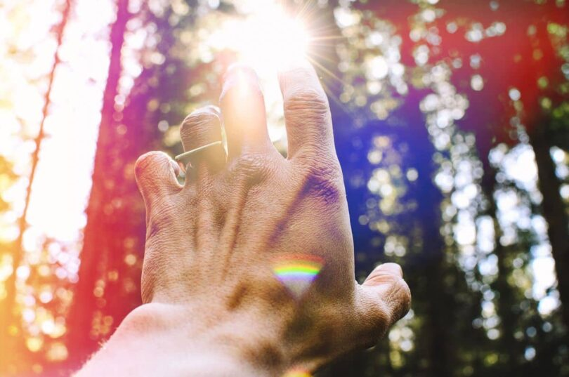 Image of a man reaching for the sun symbolic of soul communication