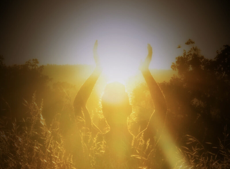 Image of a woman standing in yellow sunlight