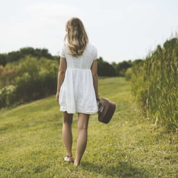 Image of a woman walking in a field with an instrument in her hand