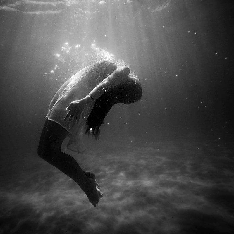 Image of a woman drowning in water symbolic of the dark night of the soul