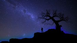 Image of a lonely man standing on a dark hill experiencing a dark night of the soul