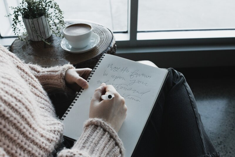 Image of a relaxed person sitting down in a chair and journaling