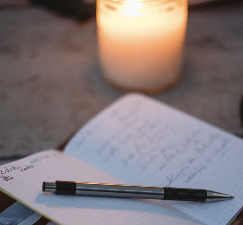 Image of a candle next to a journal