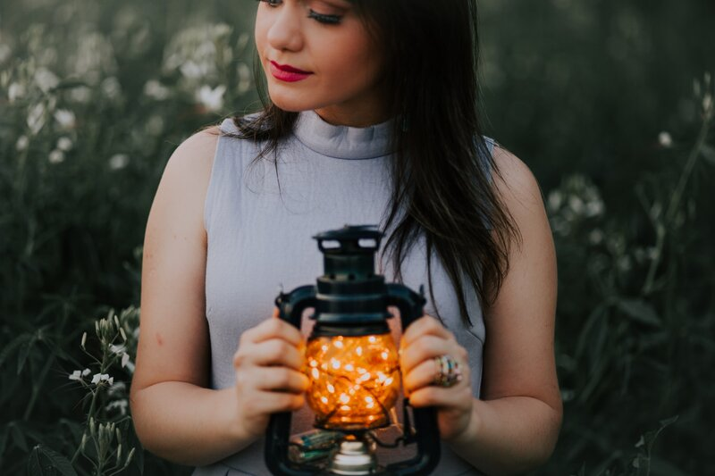 Image of a woman holding a lantern in a field of flowers