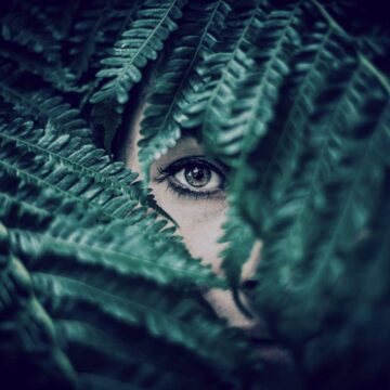 Image of a mysterious woman staring through a leaf