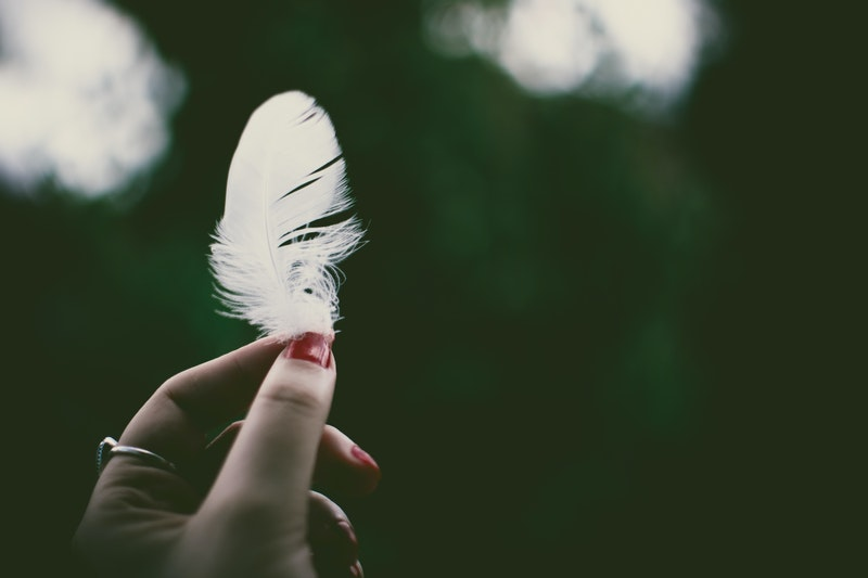 Image of a woman holding a feather which is a sign of synchronicity