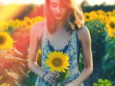 Image of a woman holding a sunflower symbolic of solar plexus chakra healing