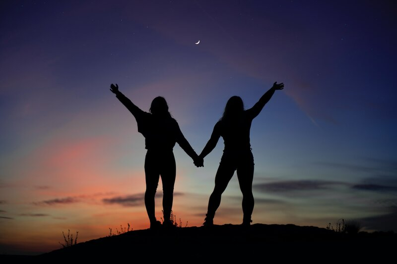 Image of two women standing together at sunset