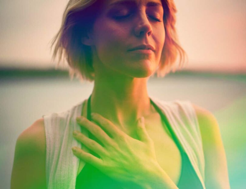 Image of a woman holding her hand to her heart chakra