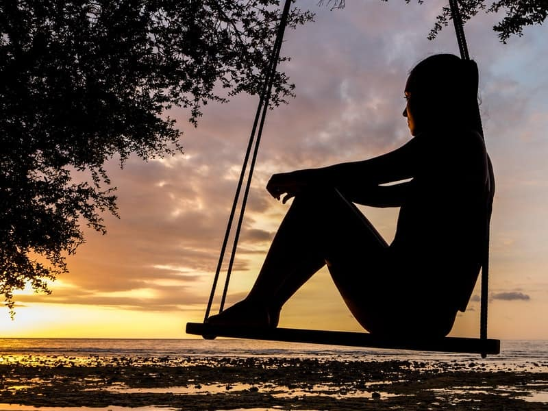 Image of a person sitting on a swing quietly learning how to trust their intuition