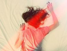 Image of a woman lying in bed with muscle tension