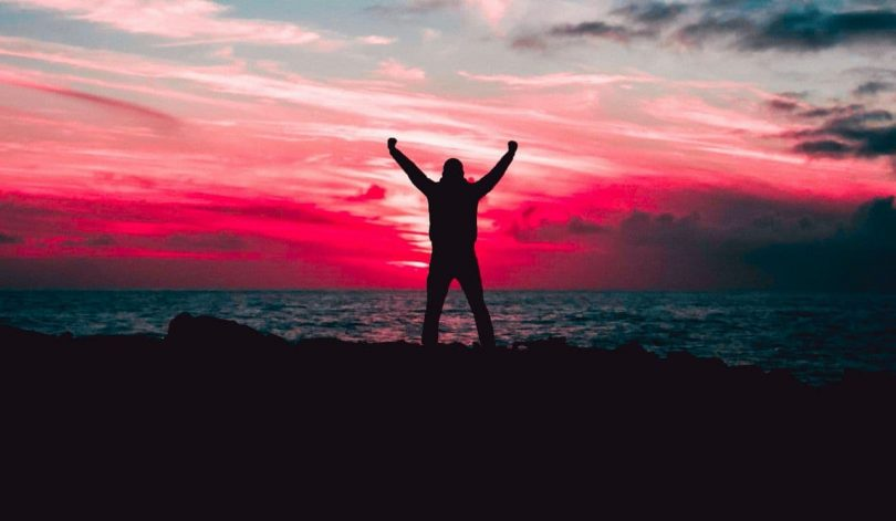 Image of a happy person near the ocean at sunset bursting with inner strength
