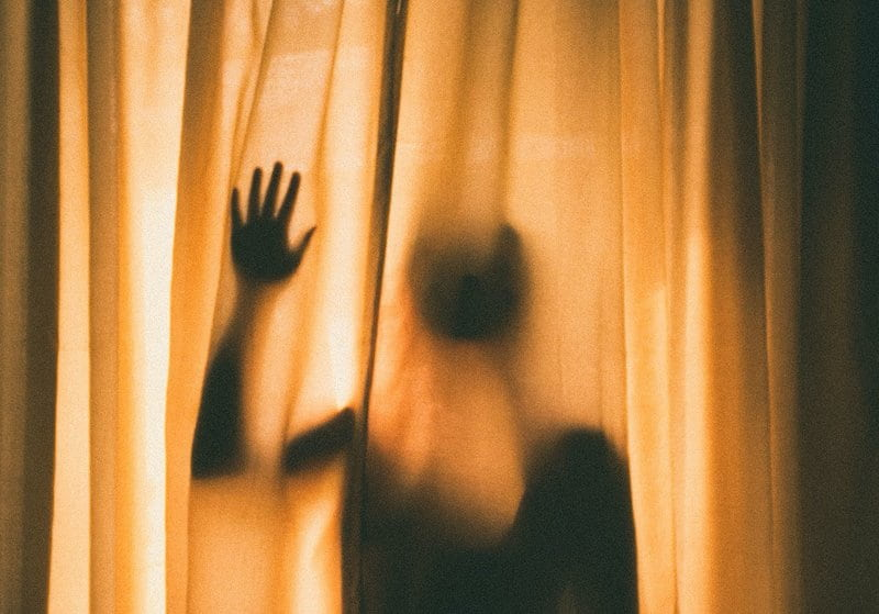 Image of a traumatized shadow ghost behind the curtains