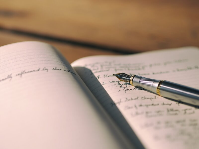 Image of a person's journal and ink pen