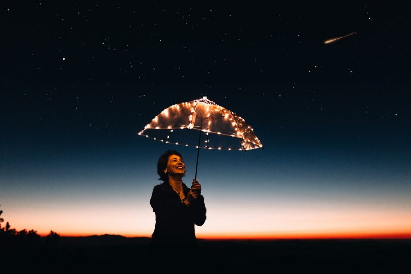 Image of a woman holding an umbrella smiling learning how to be true to herself
