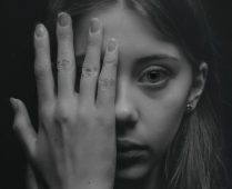 Image of a woman with her hand over her face experiencing emotional numbness