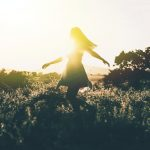Image of a woman in a flower field dancing symbolic of non-attachment