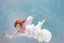 Image of a woman floating in the water symbolic of non-attachment