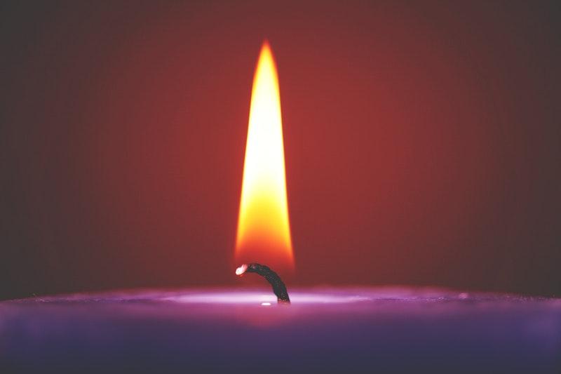Image of a purple candle burning symbolic of spiritual healing