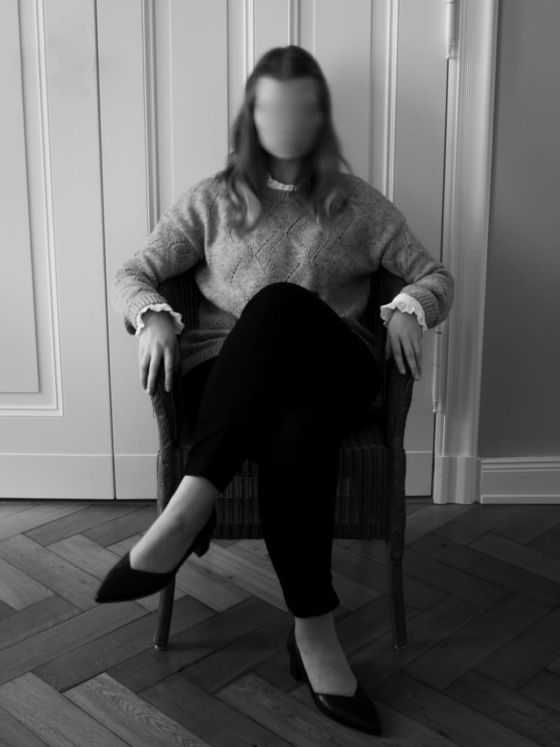 Image of a woman sitting with no face