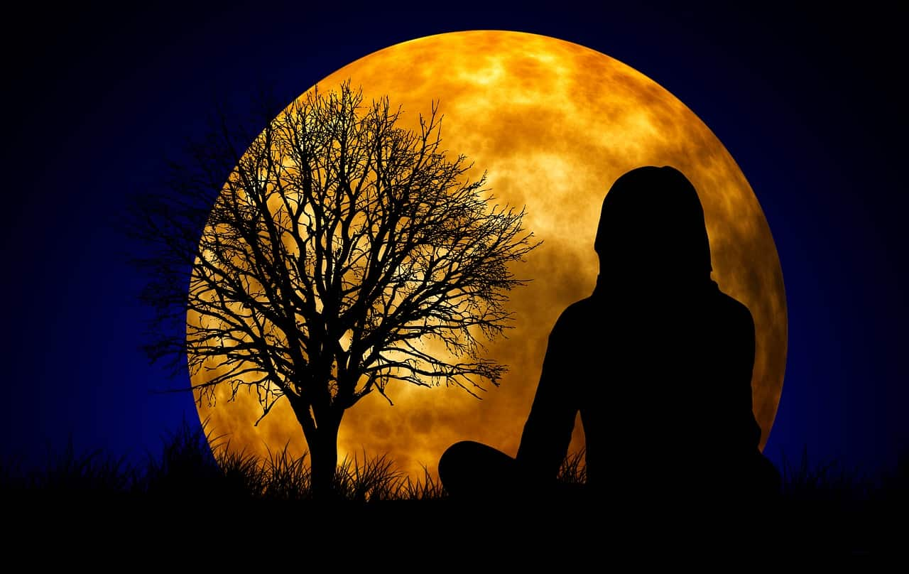 Image of a woman sitting in front of a moon experiencing oneness and wholeness