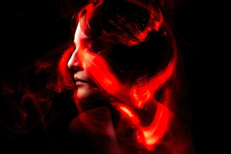 Image of a woman with red tendrils of dangerous energy around her head