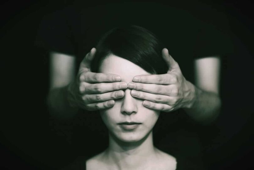Image of a woman with hands covering her eyes blocking her spiritual discernment