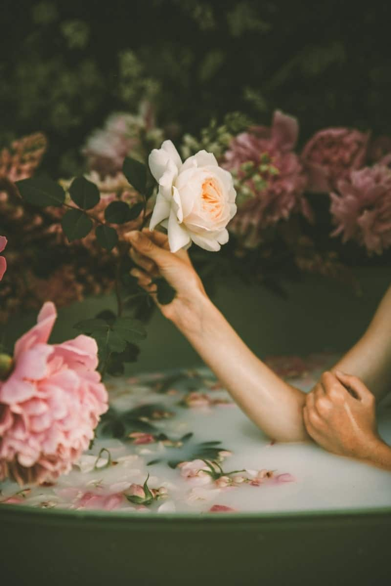 Image of a sensual woman in a bathtub surrounded by roses