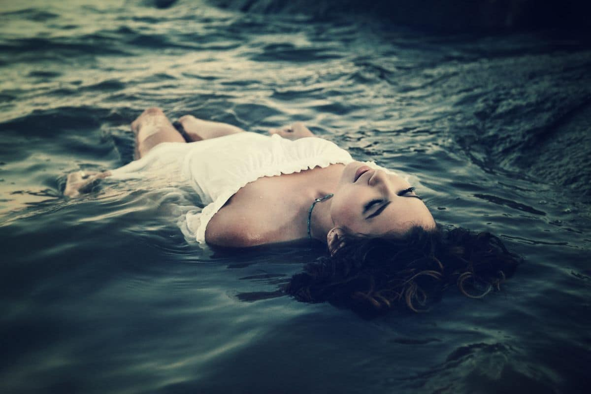 Image of a woman lying in the ocean emotionally regulating