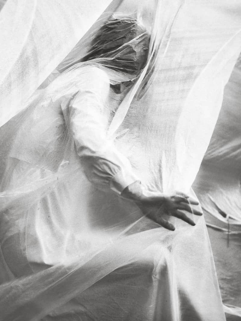 Image of a woman avoiding conflict in a white curtain