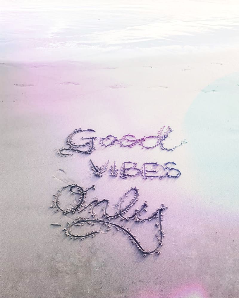 Image of good vibes only drawn into beach sand