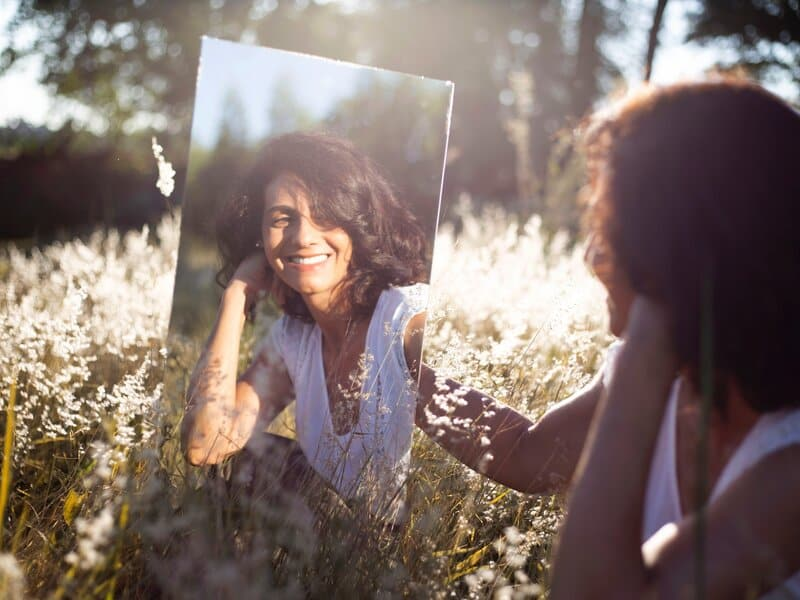 Image of a woman smiling into a mirror practicing mirror work