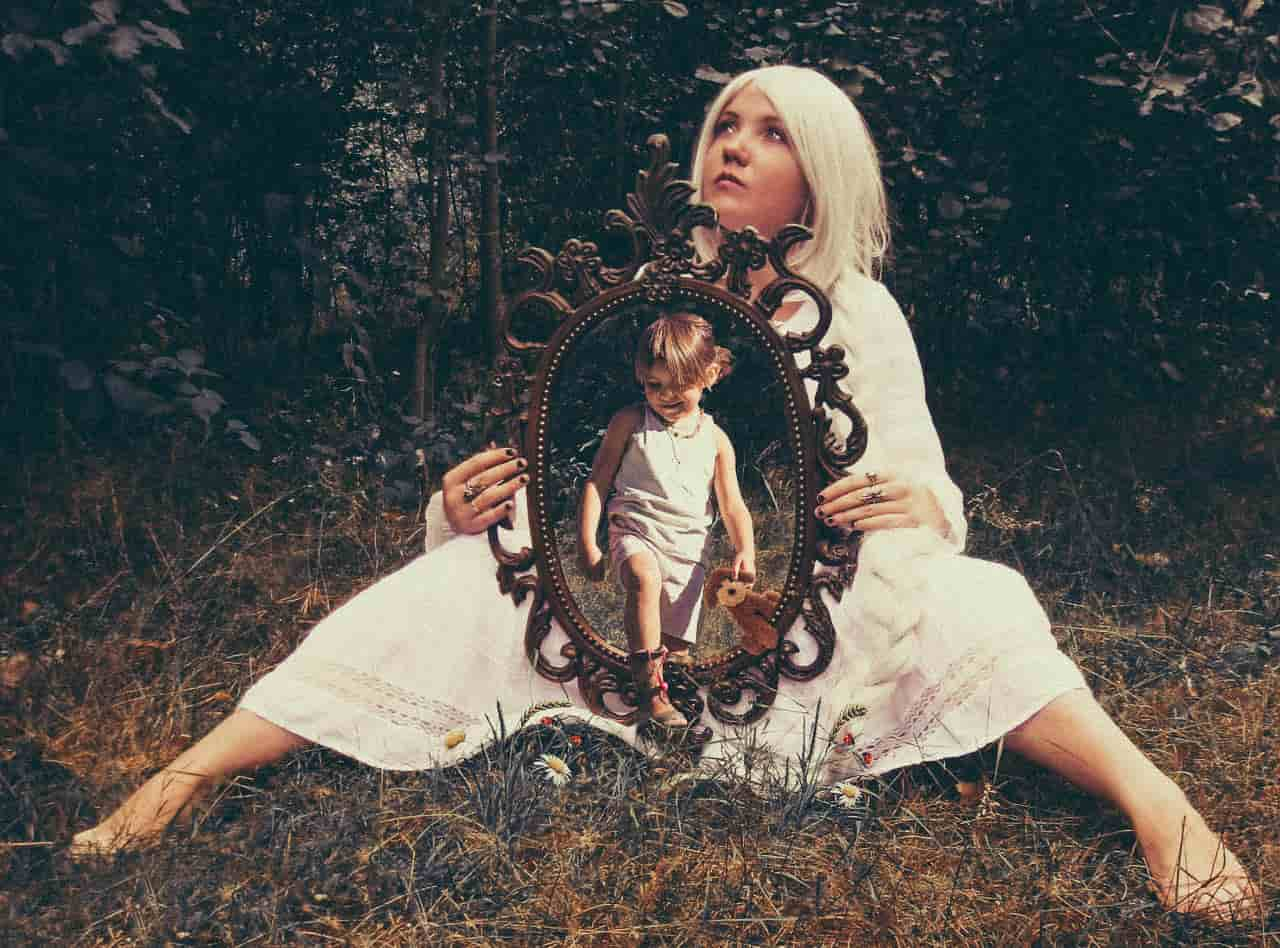 Image of a woman holding a mirror doing inner child work