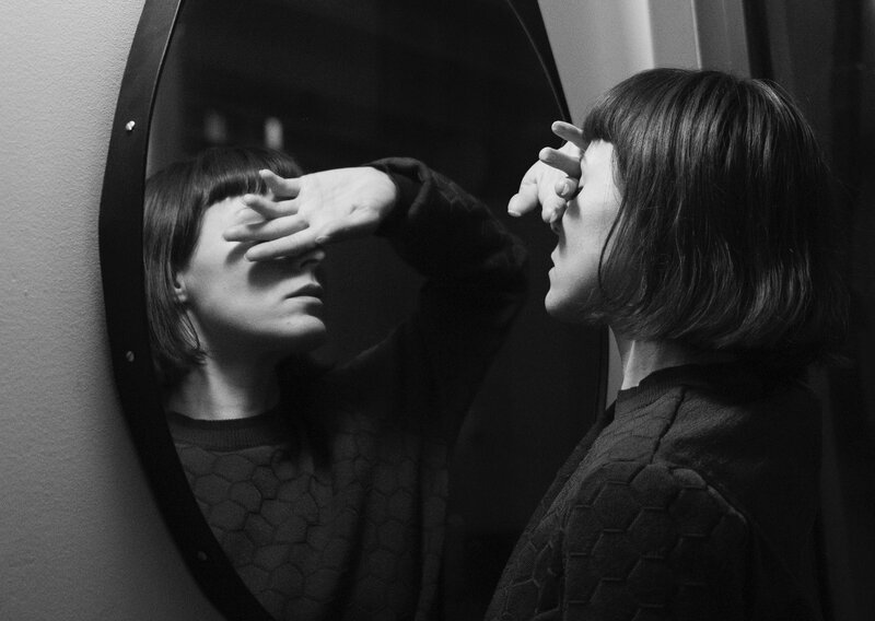 Image of a woman standing in front of a mirror feeling uncomfortable
