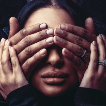 Image of a woman's face being covered by someone's hands symbolic of toxic enmeshment