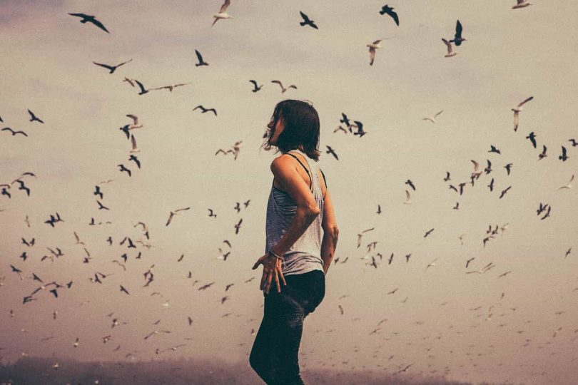 Image of woman with birds feeling her gut instinct