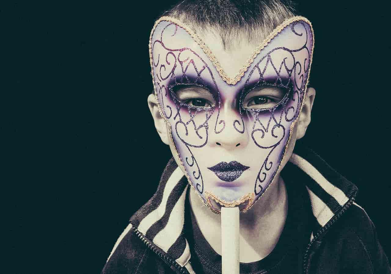Image of a boy holding up archetype mask