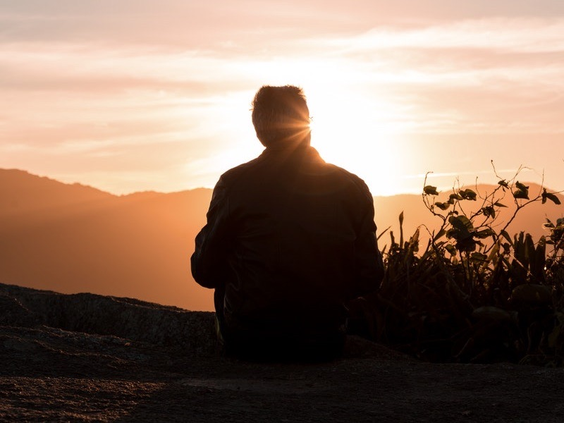 Image of a man sitting in front of the sunset
