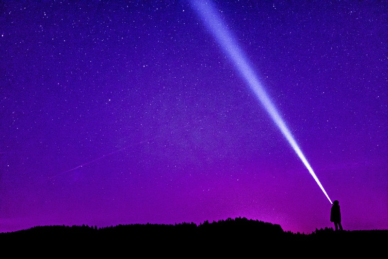 Image of a person with a flashlight against a purple sky