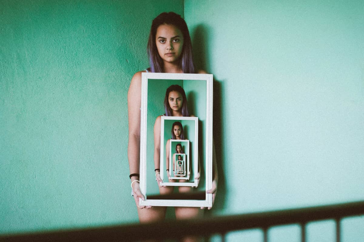 Image of a woman holding a mirror symbolizing how to find yourself