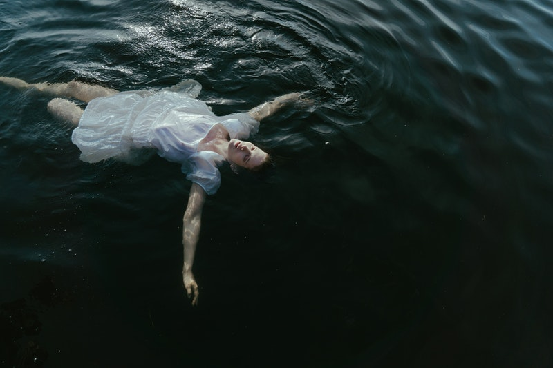 Image of a depressed woman floating on a dark sea