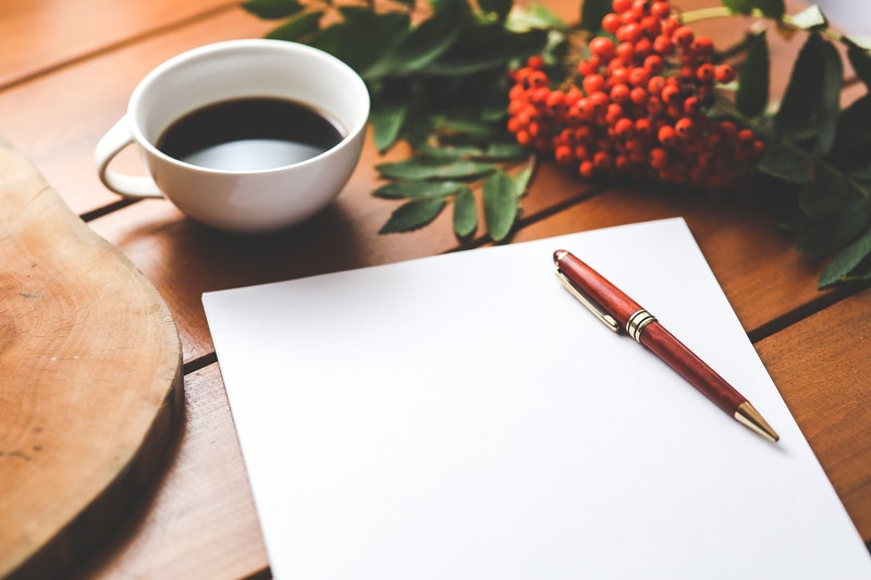 Image of a piece of paper, pen and cup of tea