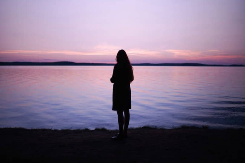 Image of a woman in front of a lake soul searching