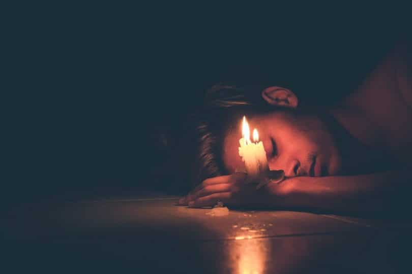 Image of a depressed man and a candle symbolic of the spiritual emergency