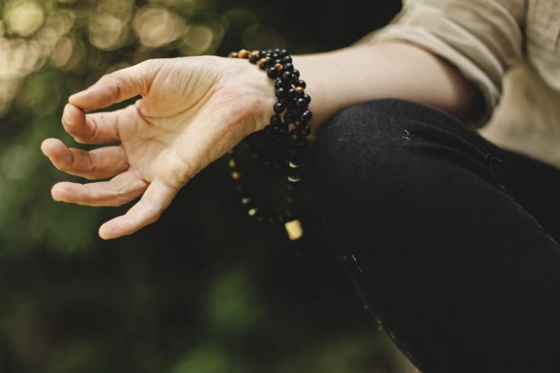 Image of a meditation person doing a mudra representing spiritual materialism