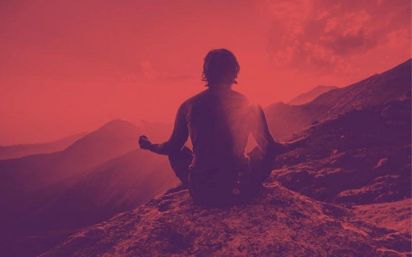 Image of a man meditating on a mountain top