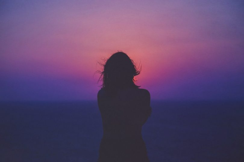 Image of a solitary woman in front of a sunset trying to learn how to deal with loneliness