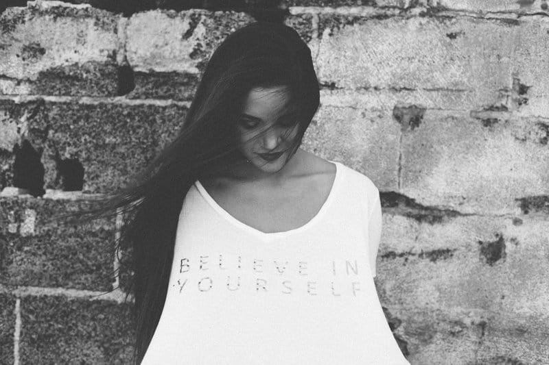 Image of a woman holding a t-shirt that says Believe in Yourself