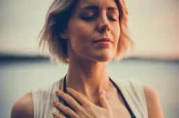 Image of a woman practicing breathwork with her hand over her heart